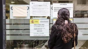 Una mujer consulta los papeles enganchados en una oficina de extranjería en Barcelona.