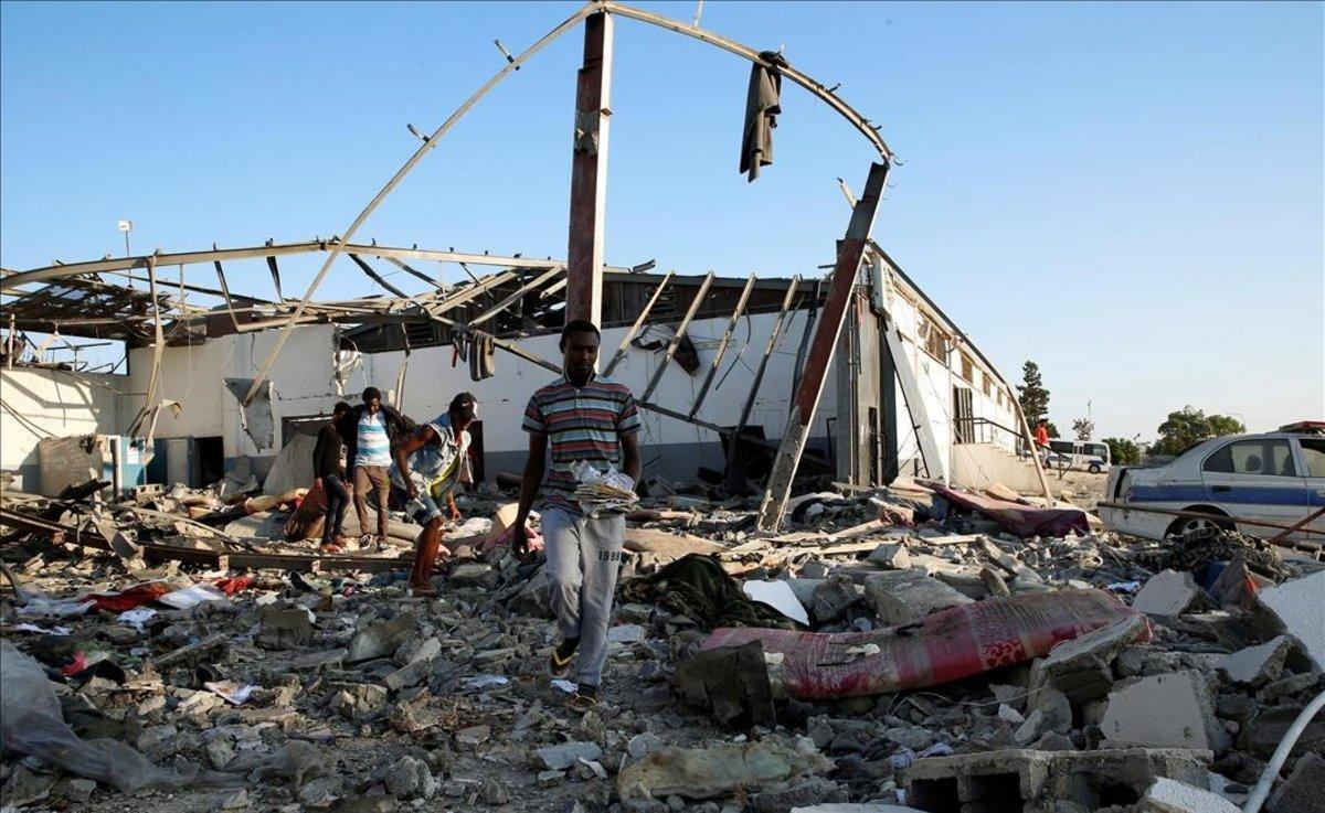 Inmigrantes recogen lo que queda de sus pertenencias tras el ataque aéreo sufrido en Trípoli.