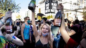 Estadounidenses celebran con 'champagne' la derrota de Donald Trump muy cerca de la Casa Blanca, este sábado.