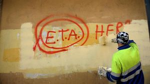 Un operario borra una pintada en la que aún se puede leer ETA