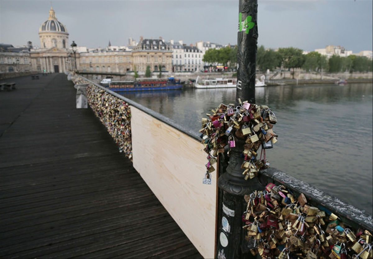 El Puente de las Artes de París, lleno de candados y con el tablón que cubre la parte que ha cedido, este domingo.