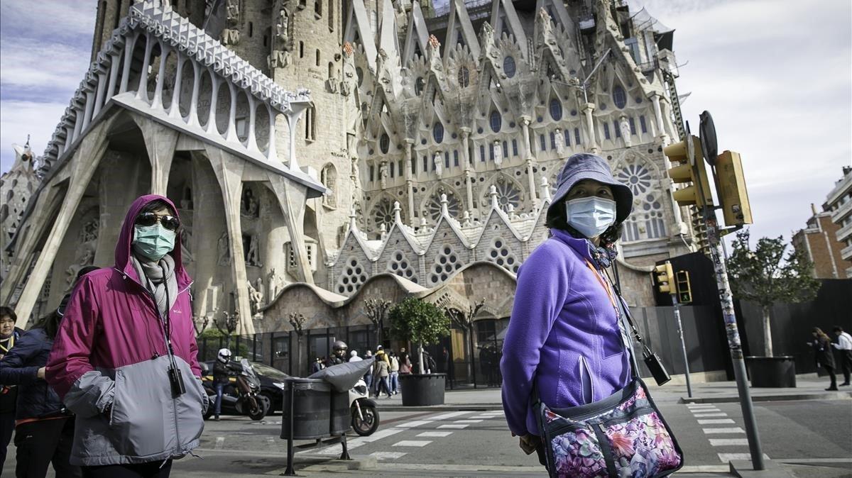 Turistas con mascarillas frente a la Sagrada Família, en Barcelona, este jueves.