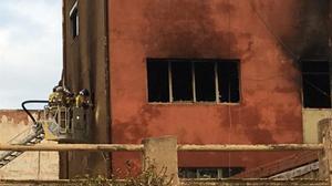 Los bomberos trabajan en la extinción de la nave ocupada en Badalona.