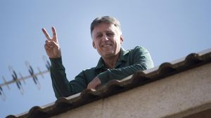 Salvi Huix, haciendo el símbolo de la victoria en su balcón tras recuperarse del coronavirus.