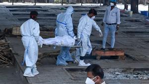 Personal sanitario traslada un cadáver de una persona fallecida por COVID-19 para su cremación, en Nueva Delhi (India). por COVID-19 para su cremación, en Nueva Delhi (India).AFP