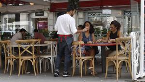 Untrabajador de la hostelería, uno de los sectores más castigados por la crisis del coronavirus,atiende a unos clientes en Barcelona.