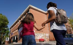 Una mamá acompaña a su hija al colegio.