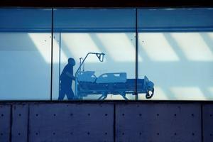 Un celador transporta una camilla por un pasillo del Hospital de Bellvitge.