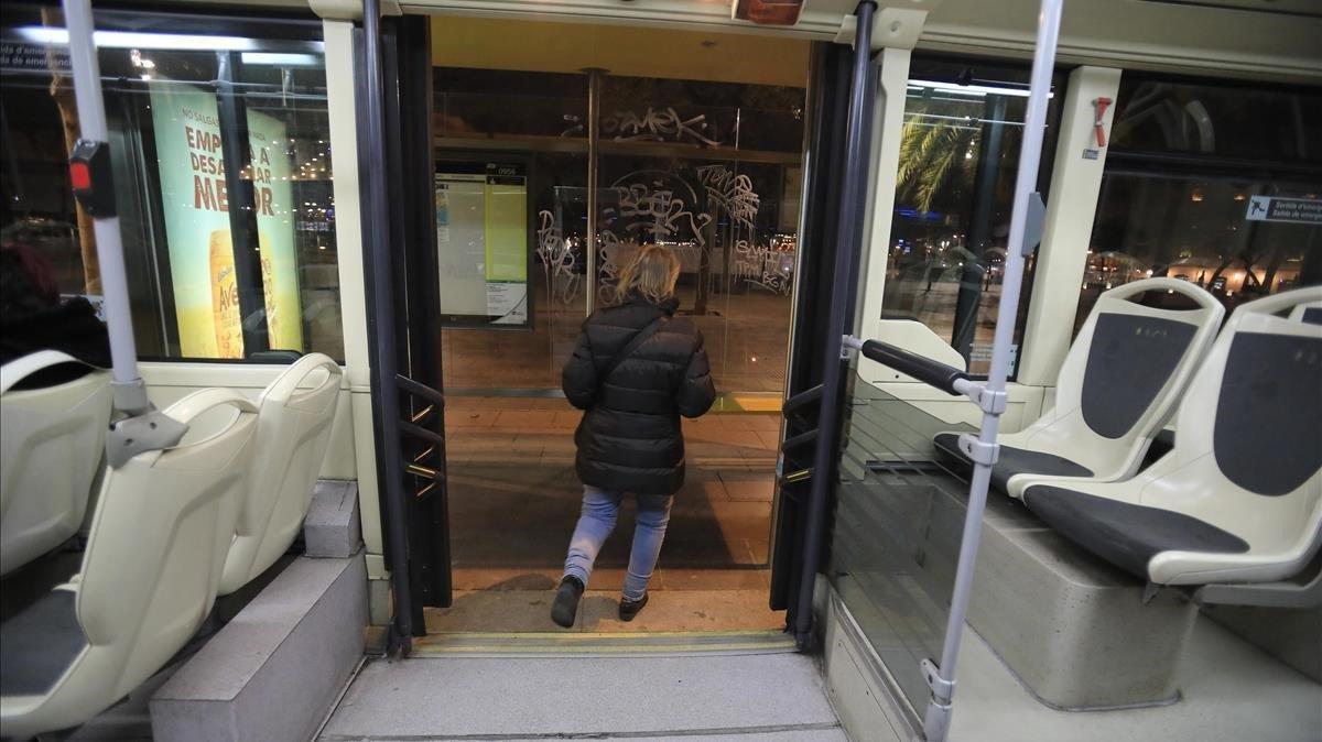 Una mujer baja de un autobús nocturno, en Barcelona.