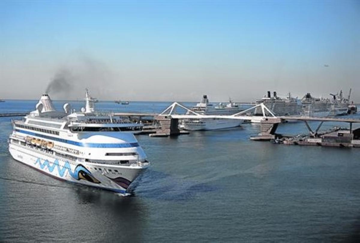 Un ferri humeante entra por la Bocana Nord junto al muelle Adossat, repleto de grandes cruceros.