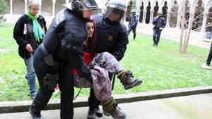 Dos agents desallotgen una manifestant a la Universitat de Girona.