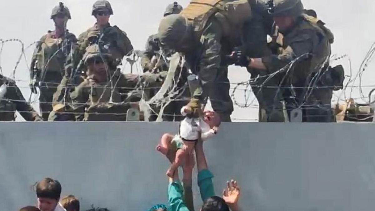 Un bebé es entregado al ejército estadounidense sobre el muro perimetral del aeropuerto para que sea evacuado, en Kabul.