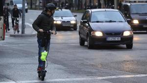 Un hombre circulando en un patinete eléctricopor una vía urbana.