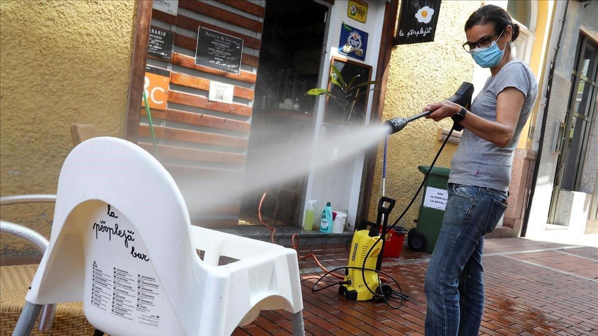 La propietaria de un bar desinfecta con agua y lejía una trona en Las Palmas.