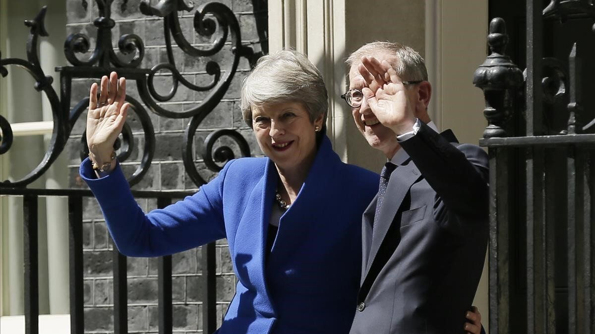 Theresa May junto a su marido Philip May saludan tras abandonarDowning Street.