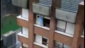 Una mujer aparece limpiando las ventanas del último piso de un edificio.
