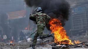 Un agente antidisturbios salta una barricada en llamas levantada por seguidores del opositor Raila Odinga, en Mathare (Nairobi), el 12 de agosto.
