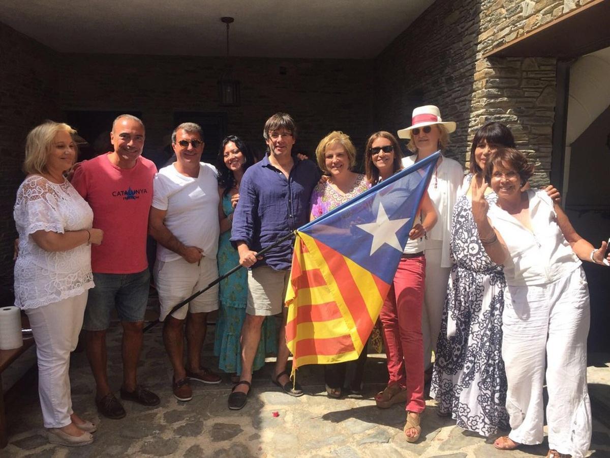 El 'president' Puigdemont, con vestuario veraniego y sosteniendo una estelada, junto a Rahola, Laporta y otros amigos en Cadaqués.