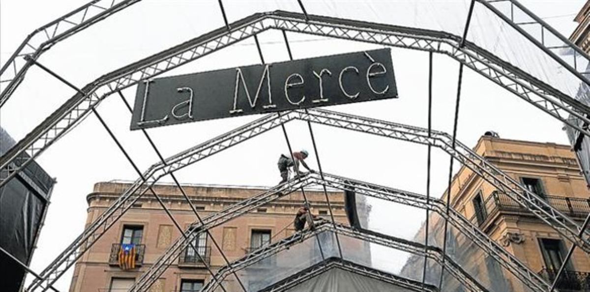 Unos operarios instalan el escenario de la plaza de Sant Jaume para las fiestas de la Mercè, ayer.