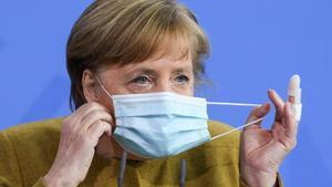 La cancillera alemana, Angela Merkel, se retira la mascarilla antes de la comparecencia que ha ofrecido este martes para explicar el proyecto de ley aprobado por el Gobierno.