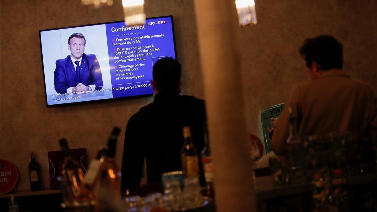 Clientes de un restaurante de París siguen el mensaje de esta noche deñ presidente francés. Emmanuele Macron.