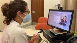 Una sanitaria atiende vía telemática, en el hospital de Sant Pau.