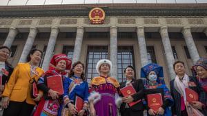 Delegados de minorías chinas con sus trajes tradicionales posan frente al edificio donde se ha celebrado el Congreso Nacional del Pueblo.