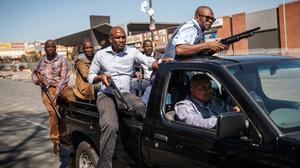 Miembros vestidos de civil del Servicio de Policía de Sudáfrica patrullan el municipio de Alexandra en Johannesburgo