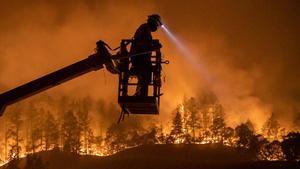 25 muertos y miles de evacuados por los incendios de California. En la foto, un empleado de una compañía de comunicaciones trabaja en la instalación de fibra óptica en una zona afectada por el incendio, en Calistoga (California).