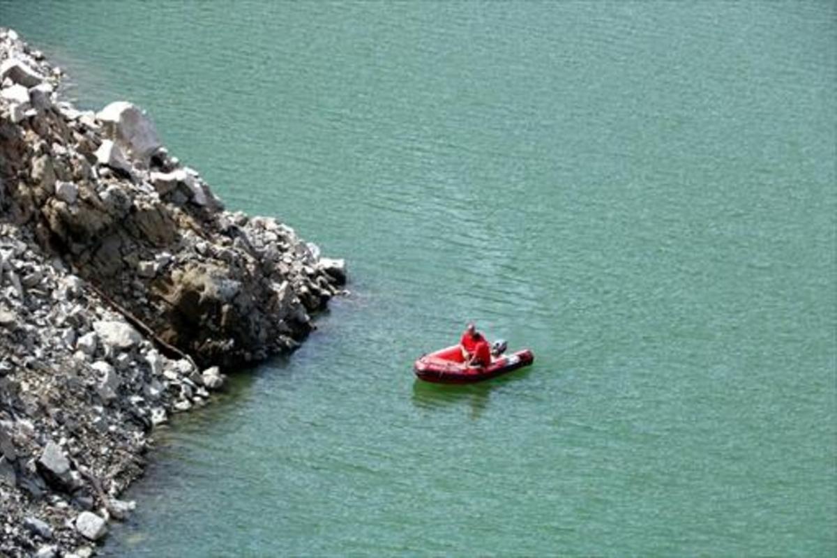 Una embarcación rastrea el perímetro del pantano de Susqueda, ayer.