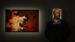Ronaldo Schemidt posa junto a la fotografía con la que ha obtenido el primer premio del World Press Photo, en la exposición sobre las imágenes galardonadas en el CCCB.