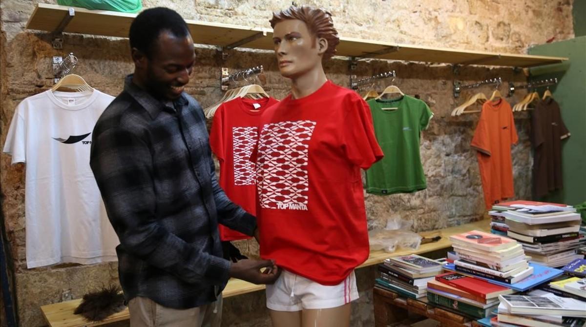 Aziz viste un maniquícon uno de los nuevos modelos de 'Top Manta'.