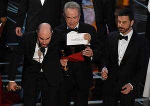 El productor de 'La La Land',Jordan Horowitz muestra la tarjeta que dice que 'Moonlight' es la ganadora, ante la mirada de Warren Beatty y Jimmy Kimmel.