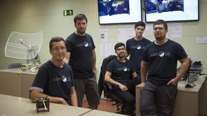 El profesor Adriano Camps (izquierda) y otros jóvenes miembros del equipo del NanoSat Lab de la UPC que ha desarrollado el nanosatélite.