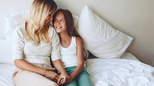 Madre e hija conversan juntas en la cama.