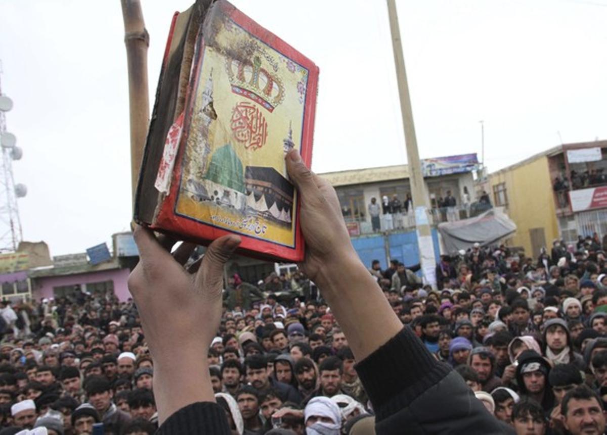 Un manifestante muestra el Corán supuestamente quemado por un soldado estaounidense.