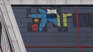 Trabajadores cambian el logotipo de Bankia por el de CaixaBank en la Torre Kio.