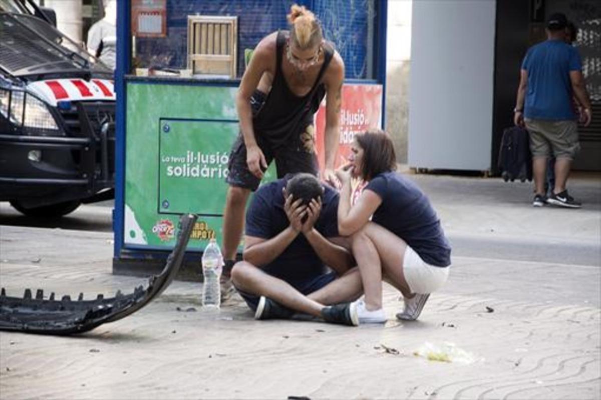 Tres transeúntes que paseaban por la Rambla cuando se produjo el atentado,junto a restos de la furgoneta utilizada por los terroristas.