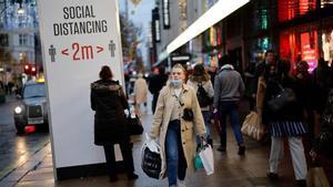 Una mujer pasea por la céntrica Oxford Street, en Londres, entre carteles que piden distancia social.