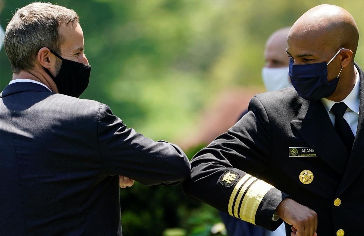 El cirujano general de los EEUU, Jerome Adams, golpea el codo con el CEO de la Corporación Financiera de Desarrollo Internacional, Adam Boehler, durante un evento de respuesta a la pandemia.