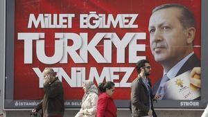 Varias personas pasan por delante de un cartel electoral de Erdogan, este jueves en Estambul.