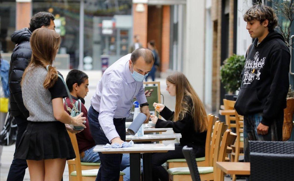 Un camarero con mascarilla en un restaurante de Londres.