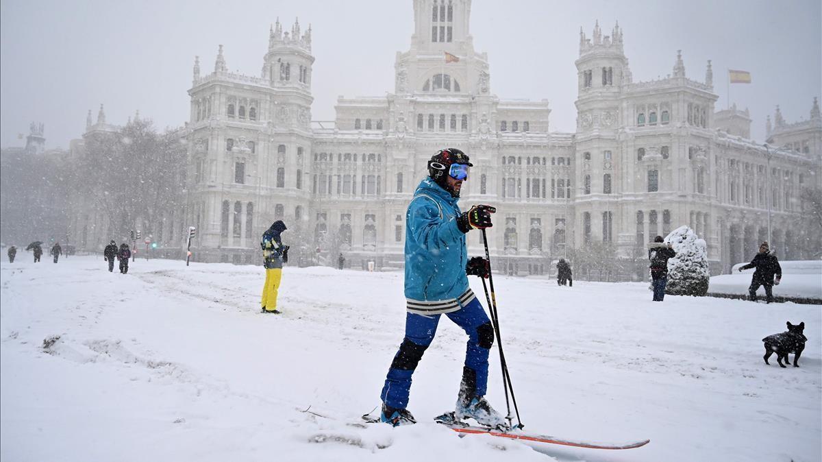Un hombre con los esquís en la Plaza de la Cibeles de Madrid