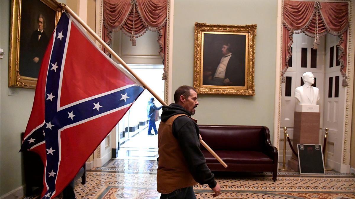 Un participante en el asalto al Capitolio de EEUU pasea por el edificio con una bandera confederada.