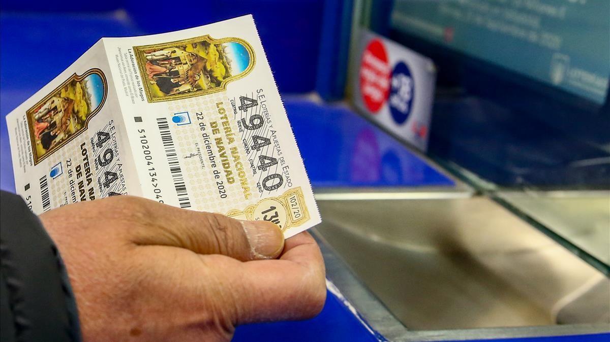 Una persona compra un decimo para el Sorteo Extraordinario de la Loteria de Navidad 2020