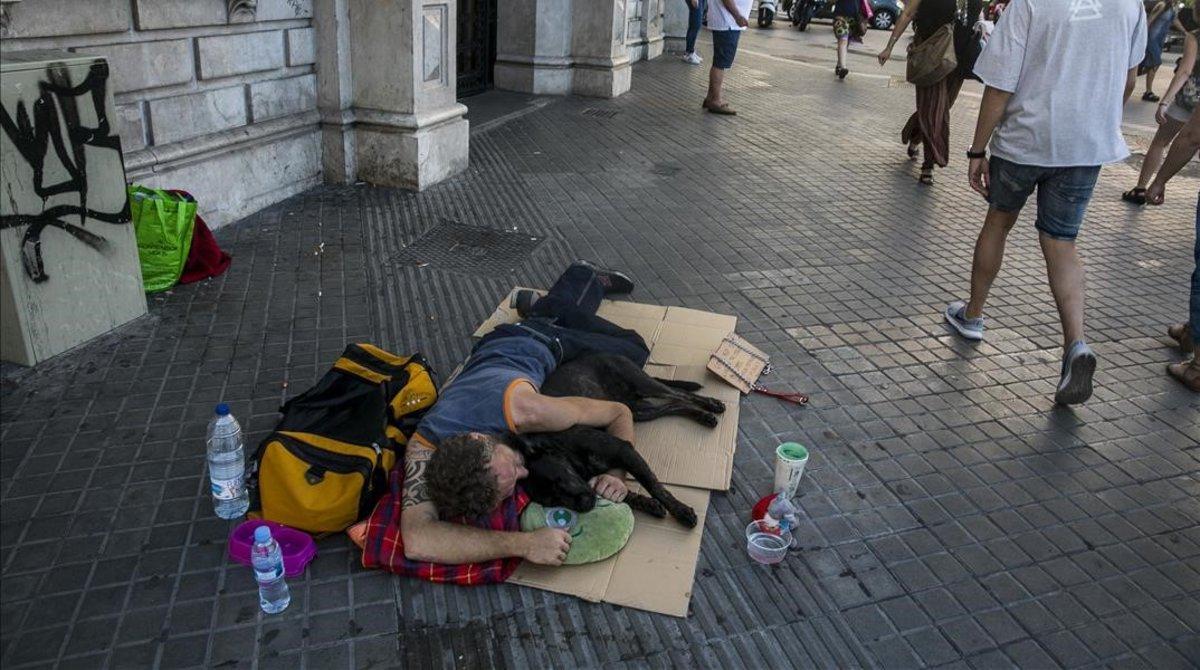 Un sintecho duerme en plena calle enla Rambla de Catalunya con Plaza de Catalunya.