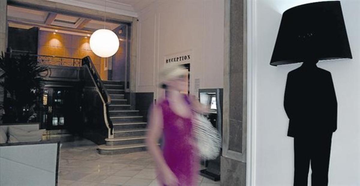 Una turista sale del portal del piso turístico en el que se aloja en el centro de Barcelona.