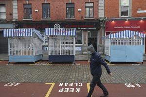 Una persona camina por una calle desierta en el centro de la ciudad de Dublín, el martes 20 de octubre de 2020.