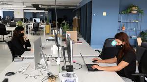 Dos empleadas en una oficina, junto a otros escritorios vacíos.