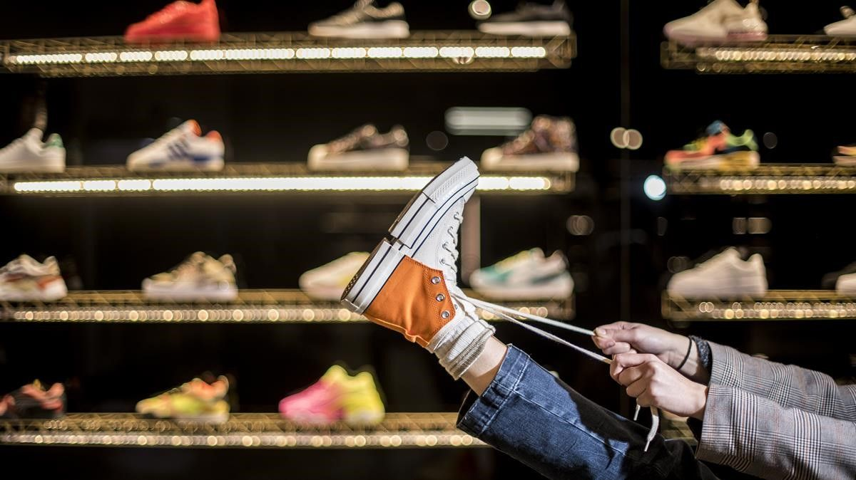 Una chica se prueba una zapatillas último modelo en el 'templo' de las 'sneakers' en Barcelona, la tienda Si Vas Descalzo.